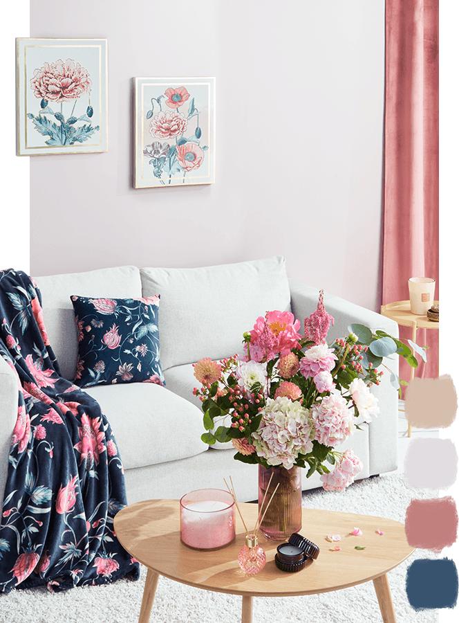 Salon. Okna z różowymi zasłonami, na ścianie obrazy w białych ramach, sztuczne kwiaty na stoliku, w środku sofa z granatową poduszką i kocem w kwiaty