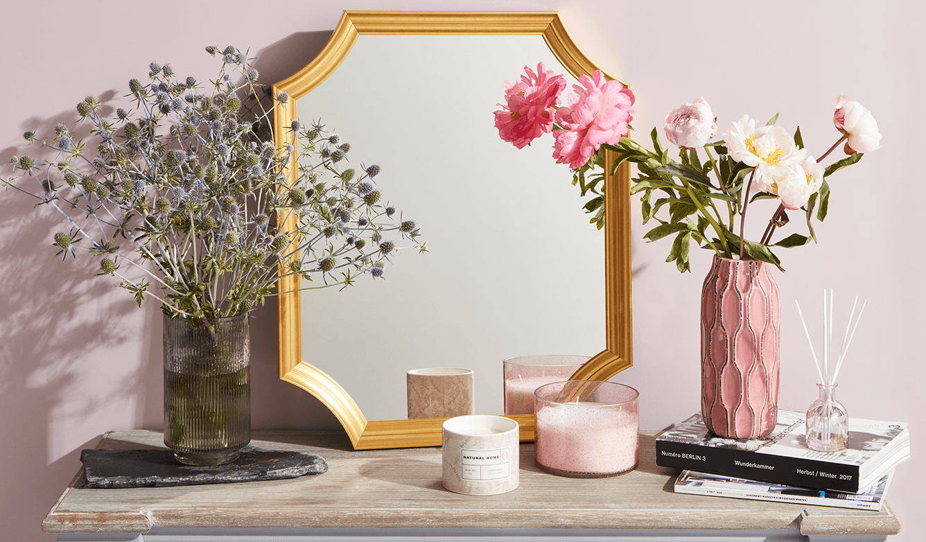 Wazony ze sztucznymu kwiatami przed lustrem w salonie